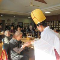 利用者の方に播磨國総社の福娘から「福銭」を手渡す様子の写真